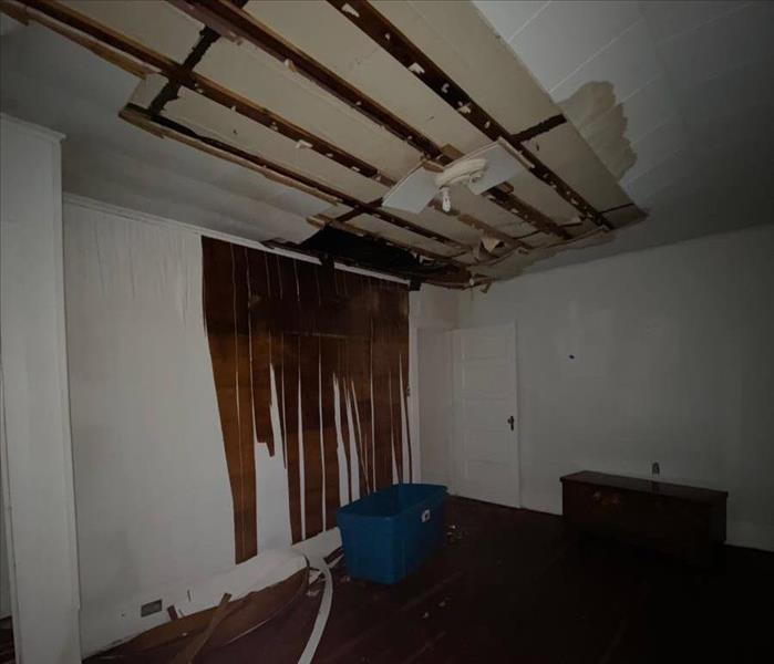 Damaged ceiling and wall in a bedroom.