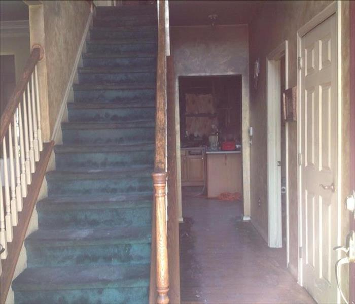 Fire Damaged staircase and entryway - soot damage on walls and stairs