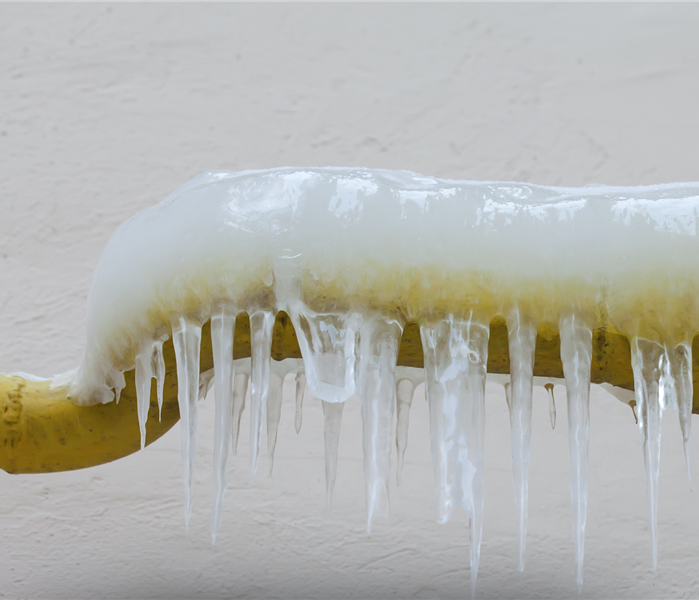 Icicles hanging from a frozen water jets, tube, yellow pipe. aged wall background. winter time concept