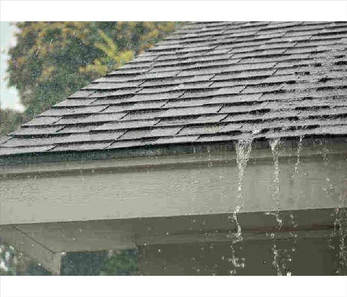 Roof with water streaming down the shingles after a rainstorm