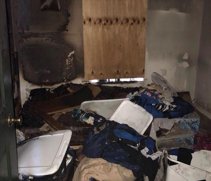 Soot damage on walls, boarded up windows, and smoke damaged clothing