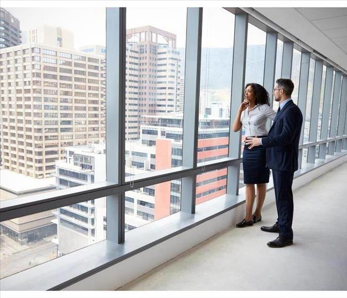 Two people looking out over a city skyline from a large office window