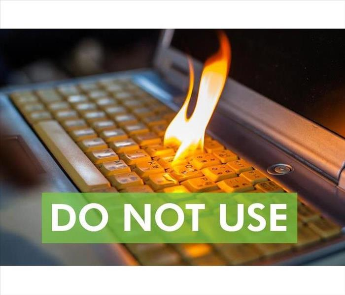 Computer keyboard with fire flame and the words DO NOT USE