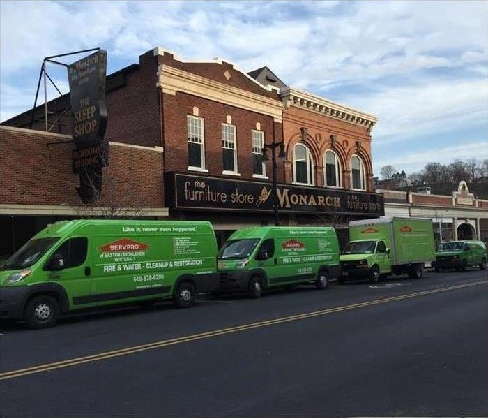 Three green SERVPRO vans parked in front of a furniture store