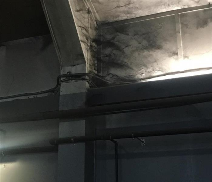 Photo depicting carbon webs in the corner of a residential structure due to fire damage